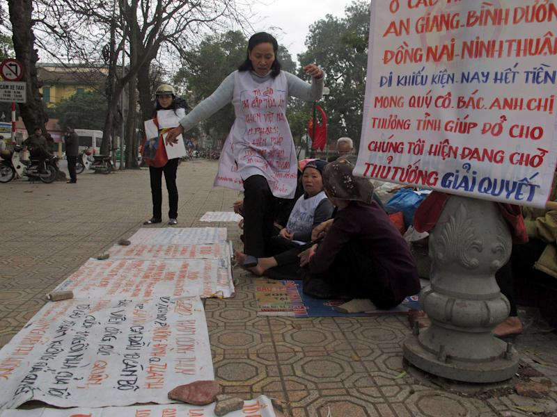 """Vietnamese women protest the seizure of their land by the government Thursday, Jan. 31, 2013 in Hanoi, Vietnam. Forced evictions are one of the main drivers of public anger against Vietnam's Communist leadership. Land disputes break out elsewhere in Asia, notably next door in China, but they have particular resonance in Vietnam, where wars and revolutions were fought in the name of the peasant class to secure collective ownership of the land. A banner reads: """"People from provinces of An Giang, Binh Duong, Dong Nai and Ninh Thuan who are filing their petitions, now spend all their money. We would like you to show your love to help us. We are waiting for the prime minister to solve."""" (AP Photo/Chris Brummitt)"""
