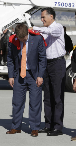 Republican presidential candidate and former Massachusetts Gov. Mitt Romney uses aide Garrett Jackson's back to sign a shirt for a volunteer before he boards his campaign plane in San Francisco,Saturday, Sept. 22, 2012. (AP Photo/Charles Dharapak)