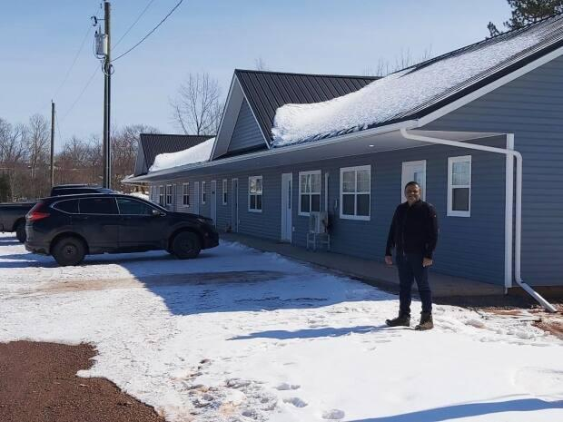 Punnapadam, president of Confederation Construction and Interiors Inc., stands in front of one of the two new six-unit buildings constructed in Belfast, P.E.I.