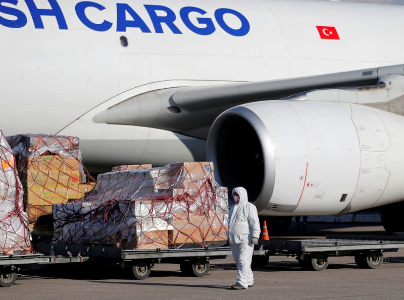 A worker unloads a shipment of medical supplies from Turkey intended to combat the spread of the coronavirus disease (COVID-19), at Almaty International Airport