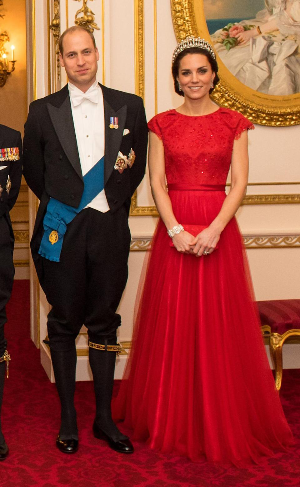 <p>The Duchess recycled yet another dress, wearing a royal red Jenny Packham gown to the 2016 annual Diplomatic Reception. First seen on her at a state banquet in 2015, the design's scarlet shade was intended to celebrate China and features Kate's favourite slim-fitting waist style. She also wore the extremely heavy Cambridge Lover's Knot tiara - which once belonged to Diana - along with chandelier earrings and a diamond bracelet given to her by William.</p><p><i>[Photo: PA]</i></p>