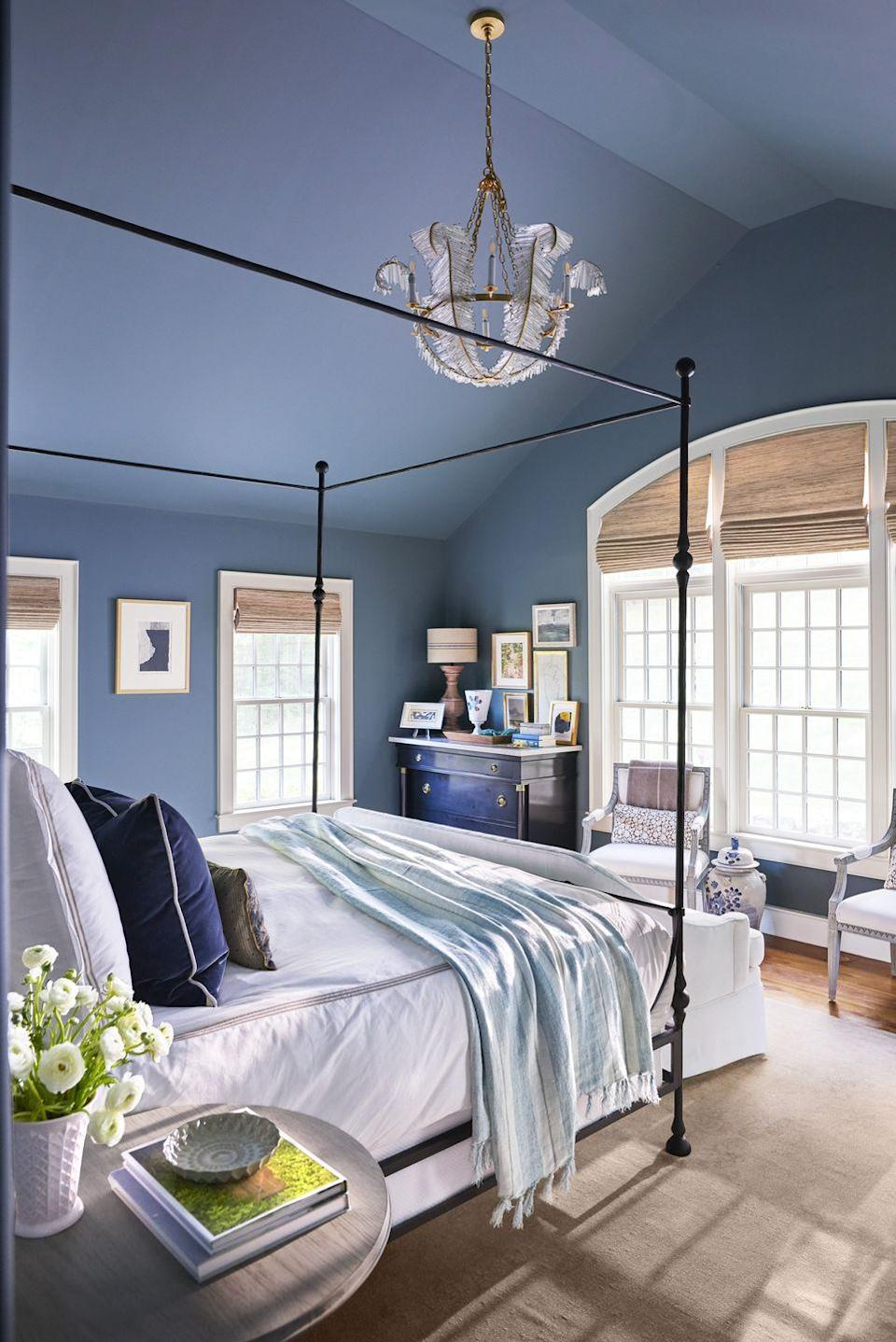 """<p>A moody blue paint color delivers your bedroom a sophisticated and serene look. """"I picked the dark blue based on a paint swatch with fears I might regret it,"""" says homeowner Debbie Propst, president of legendary furniture company Herman Miller, """"but then I read the color was 'inspired by the dramatic Scottish skies."""" Debbie, who is 100% Scottish, felt it was sign. The unexpected choice of painting the ceilings the same color as the walls created a calming cohesiveness of color, rather than a choppy feel that a jarring white ceiling would have brought. It works because of the room's high ceiling height. </p><p><strong>Get the Look: </strong><br>Wall Paint Color: <a href=""""https://go.redirectingat.com?id=74968X1596630&url=https%3A%2F%2Fwww.farrow-ball.com%2Fen-us%2Fpaint-colours%2Finchyra-blue&sref=https%3A%2F%2Fwww.countryliving.com%2Fremodeling-renovation%2Fhome-makeovers%2Fg32468539%2Fbest-bedroom-paint-colors-ideas%2F"""" rel=""""nofollow noopener"""" target=""""_blank"""" data-ylk=""""slk:Inchyra Blue by Farrow & Ball"""" class=""""link rapid-noclick-resp"""">Inchyra Blue by Farrow & Ball<br></a>Window Treatments: <a href=""""https://go.redirectingat.com?id=74968X1596630&url=https%3A%2F%2Fwww.theshadestore.com%2Fshades%2Fwoven-wood-shades&sref=https%3A%2F%2Fwww.countryliving.com%2Fremodeling-renovation%2Fhome-makeovers%2Fg32468539%2Fbest-bedroom-paint-colors-ideas%2F"""" rel=""""nofollow noopener"""" target=""""_blank"""" data-ylk=""""slk:Woven Wood Shades; theshadestore.com"""" class=""""link rapid-noclick-resp"""">Woven Wood Shades; theshadestore.com</a></p>"""