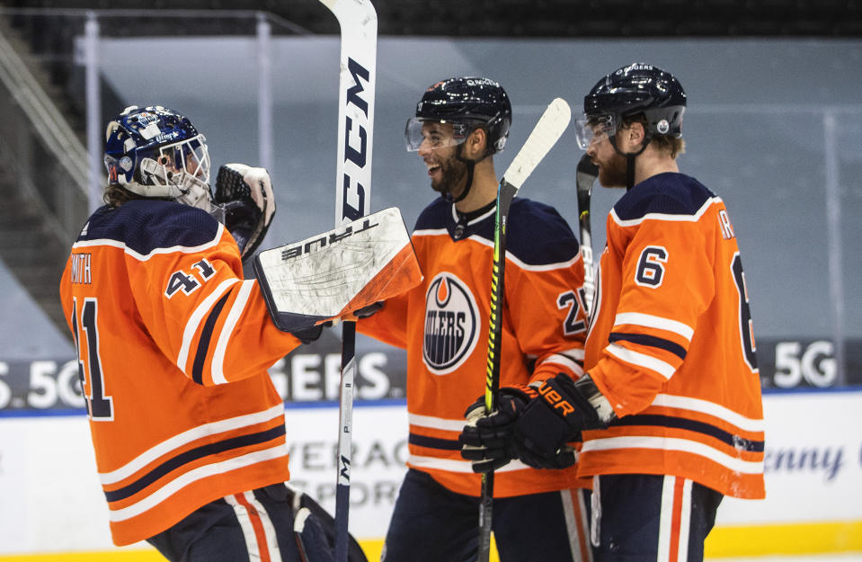 Edmonton Oilers goalie Mike Smith (41) and teammates Darnell Nurse (25) and Adam Larsson (6) celebrate the team's win over the Calgary Flames in an NHL hockey game Friday, April 2, 2021, in Edmonton, Alberta. (Jason Franson/The Canadian Press via AP)