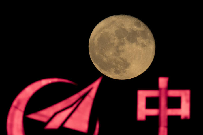 """In this photo taken Tuesday, Nov. 15, 2016, the supermoon rises over a logo for a Chinese state owned enterprise with part of the word for """"China"""" in Beijing. China's Nov. 24, 2020, trip to the moon and, presumably, back is the latest milestone in the Asian powerhouse's slow but steady ascent to the stars. (AP Photo/Ng Han Guan, File)"""