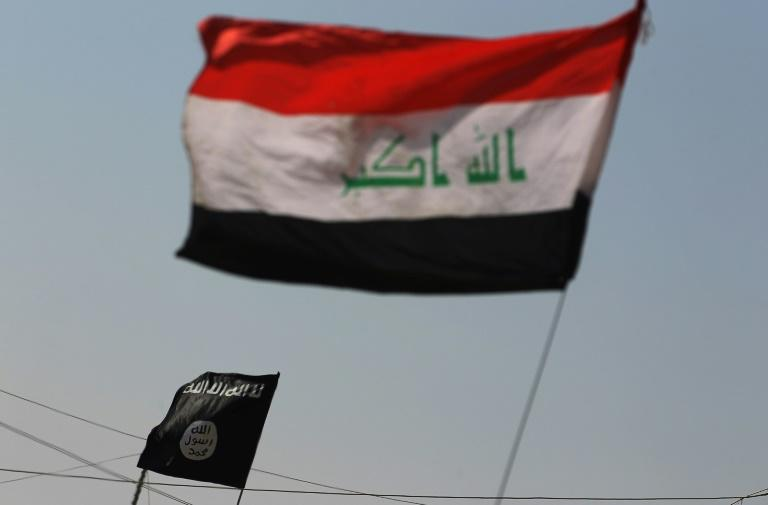 A picture of an Islamic State (IS) group flag (L) and an Iraqi national flag in the northern Iraqi town of Sharqat