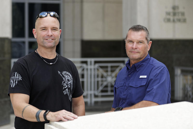 In this Thursday, Sept. 12, 2019, photo, Eric Reynolds, left, and Dave Stull, both police officers, pose for a picture in Orlando, Fla. They recently found out they were half brothers though a DNA test. (AP Photo/John Raoux)