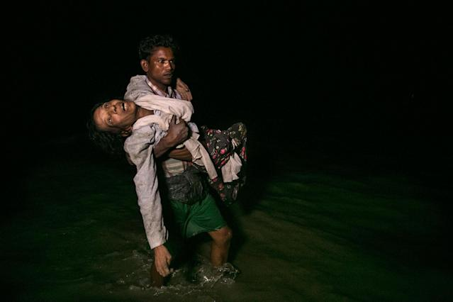 <p>Sona Banu gets carried by Nobi Hossain to the shore of the Naf river as hundreds of Rohingya arrive by boats in the safety of darkness on September 27, on Shah Porir Dwip island, Cox's Bazar, Bangladesh. (Photograph by Paula Bronstein/Getty Images) </p>
