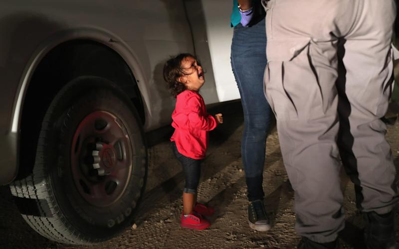 Yanela Varela Hernandez, aged two, weeps as her mother Sandra is patted down by border agents in Texas. She is currently with her mother at a shelter, her father said - Getty Images North America