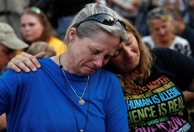 <p>Community members Carol Geithner, left, and Yasemine Jamison take part in a candlelight vigil near the Capital Gazette, the day after a gunman killed five people inside the newspaper's building in Annapolis, Md., June 29, 2018. (Photo: Leah Millis/Reuters) </p>
