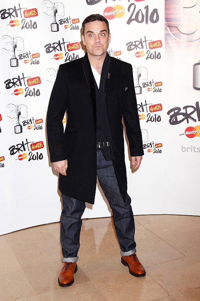 "Robbie Williams struck an awkward pose in his signature rolled up jeans and a knee-length coat. The singer was honored with the Outstanding Contribution to Music Brit award, and closed the show with a medley of his hit songs. Dave Hogan/Mission Pictures/<a href=""http://www.gettyimages.com/"" target=""new"">GettyImages.com</a> - February 16, 2010"