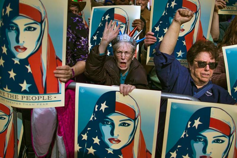 People carry posters during a rally in Times Square against Trump's order banning travel from seven Muslim-majority nations. Source: AP