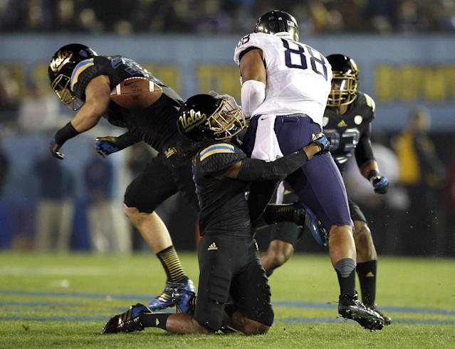 UCLA linebacker Jordan Zumwalt, back left, knocks the ball away from Washington tight end Austin Seferian-Jenkins (88) for a fumble, with UCLA safety Randall Goforth, on his knees, making the stop in the first quarter of their NCAA college football game Friday, Nov. 15, 2013, in Pasadena, Calif. UCLA recovered the ball. (AP Photo/Alex Gallardo)