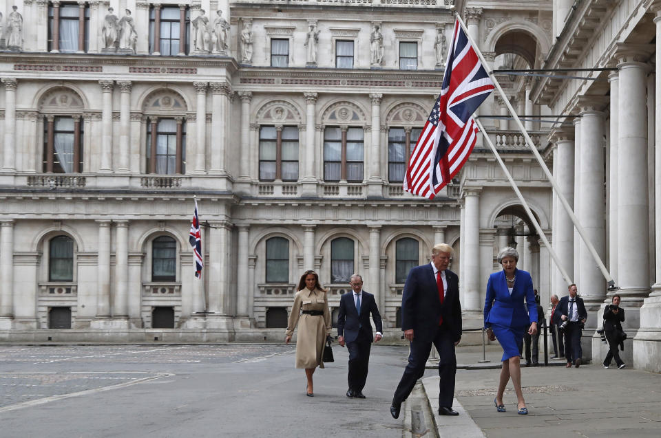 Britain's Prime Minister Theresa May, her husband Philip, President Donald Trump and first lady Melania Trump walk through the Quadrangle of the Foreign Office for a joint press conference in central London, Tuesday, June 4, 2019. (AP Photo/Frank Augstein)