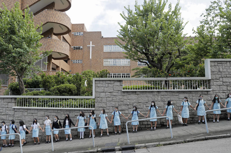 Students form human chain outside the Maryknoll Convent School in Hong Kong, Friday, Sept. 6, 2019. Hong Kong leader Carrie Lam said Thursday that the decision to withdraw an extradition bill that sparked months of demonstrations in the semi-autonomous Chinese territory was her government's own initiative to break the impasse, and not Beijing's directive. (AP Photo/Kin Cheung)