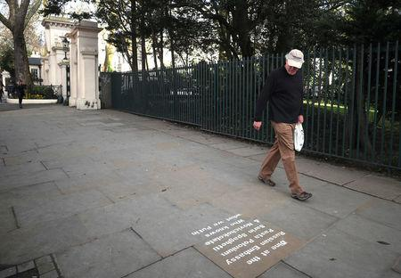 A man walks past graffiti sprayed on the pavement near the entrance to the Russian embassy and ambassador's residence in London, Britain, March 15, 2018. REUTERS/Hannah McKay