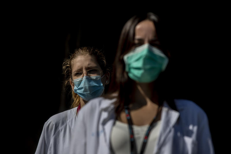 Medical staff and nurses wearing face masks to prevent the spread of coronavirus gather during a protest demanding an improvement in wages and labor conditions at the 12 Octubre hospital in Madrid, Spain, Monday, Sept. 28, 2020. Health authorities combating coronavirus in Madrid are adding a further eight areas of the Spanish capital to those with movement restrictions but have not followed a recommendation from the national government that the partial lockdown should apply to the whole city. (AP Photo/Manu Fernandez)