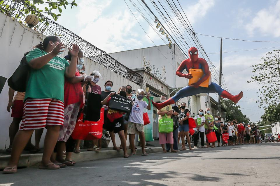 A man dressed as Spider-Man entertains people lining up for free goods for their children affected by the COVID-19 lockdown in Manila, the Philippines on April 27, 2021. (Photo: Xinhua/Rouelle Umali via Getty Images)