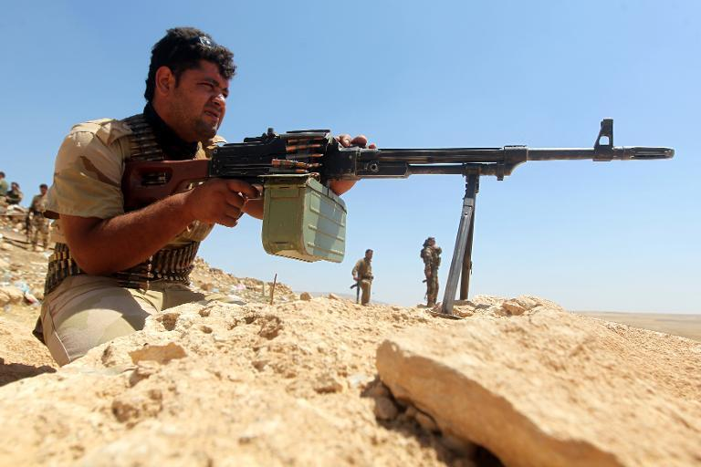 An Iraqi Kurdish Peshmerga fighter takes position on the front line in Bashiqa, north-east of Mosul on August 12, 2014