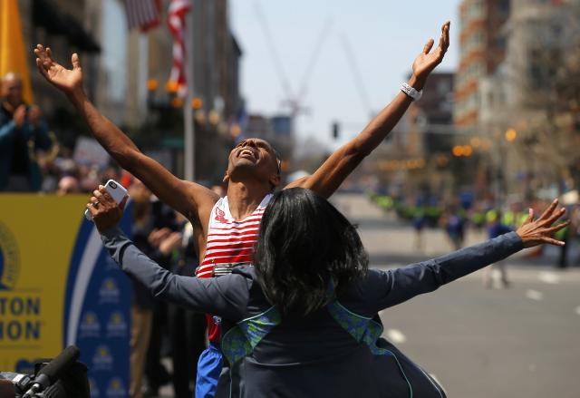 Meb Keflezighi of the U.S. celebrates with his wifre Yordanos Asgedom after winning the men's division at the 118th running of the Boston Marathon in Boston, Massachusetts April 21, 2014. REUTERS/Brian Snyder (UNITED STATES - Tags: SPORT ATHLETICS)