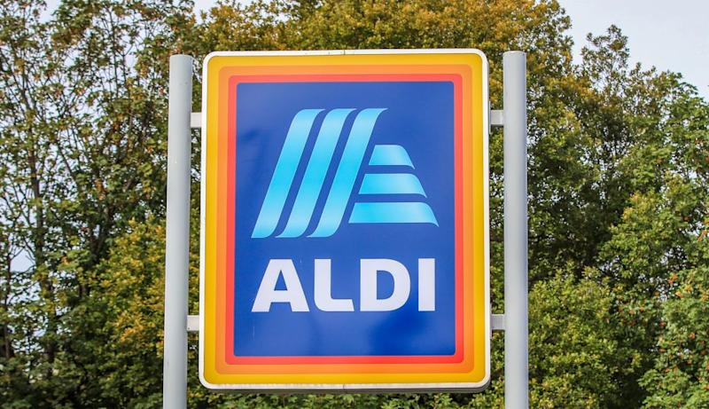 Aldi sign in front of green trees.