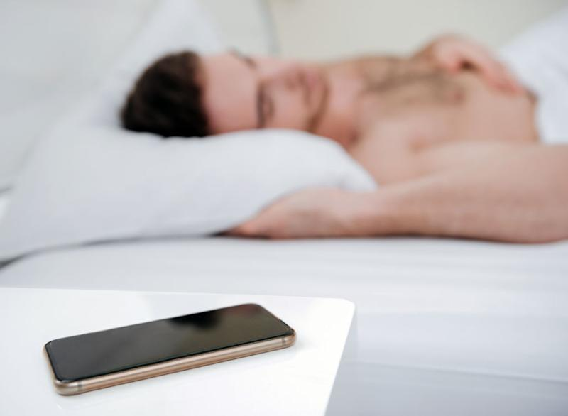 Man sleeping phone bedside