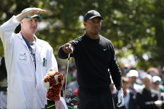 Tiger Woods of the U.S. chooses his club on the fourth tee with caddie Joe Lacava during first round play of the 2018 Masters golf tournament at the Augusta National Golf Club in Augusta, Georgia, U.S., April 5, 2018. REUTERS/Jonathan Ernst