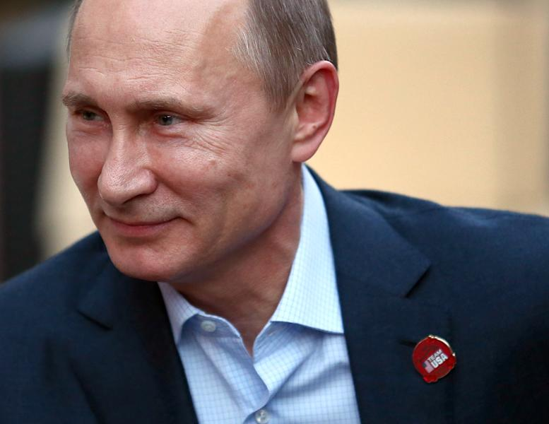 Russian President Vladimir Putin wears a Team USA pin while visiting USA House in the Olympic Village during the 2014 Winter Olympics on Friday, Feb. 14, 2014, in Sochi, Russia. (AP Photo/Marianna Massey, USOC Pool)