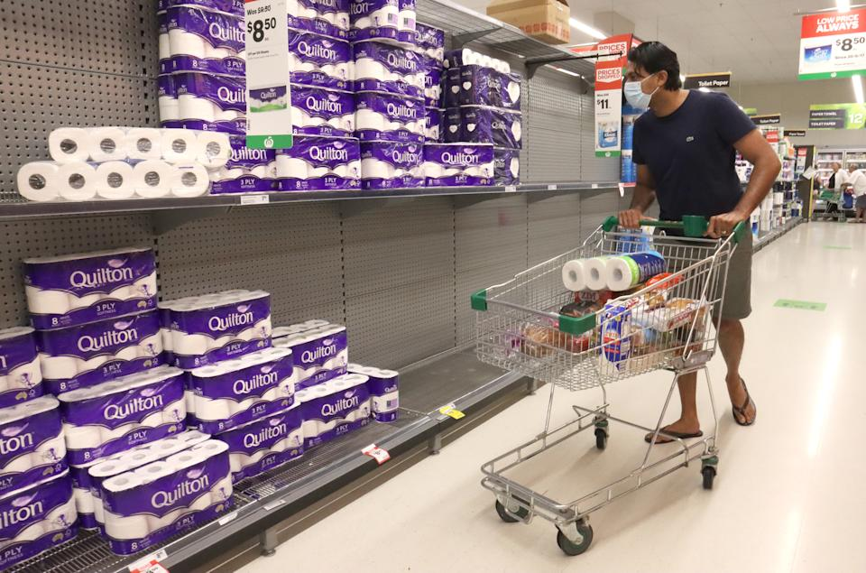 A shopper is seen in the toilet paper aisle at Woolworths.
