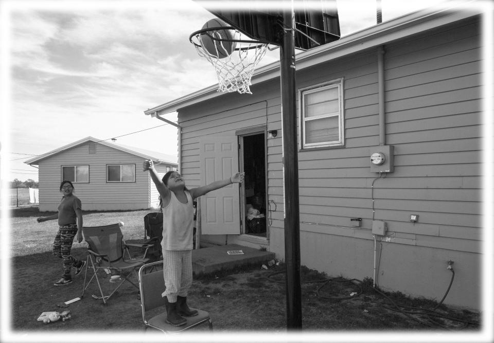 Justice Bull Shows, 13, looks on as Ariya Bull Shows, 6, makes the basket at her home on Rosebud Indian Reservation in South Dakota in 2014. (Photo: Nikki Kahn/The Washington Post via Getty Images; digitally enhanced by Yahoo News)