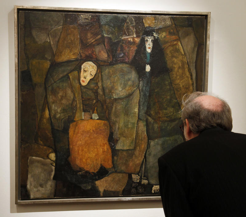 """A visitor look at the painting titled """"Procession"""" from Egon Schiele dates back to 1911 and depicts three women in different stages of their lives, in Vienna, Austria, on Wednesday, Nov. 3, 2010. Austrian auctioneers have unveiled a precious Egon Schiele painting that could fetch millions when it goes under the hammer next week. Currently owned by an unidentified American art collector, it is valued at 3.5 million euros to 7 million euros. The auction takes place Tuesday. (AP Photo/Ronald Zak)"""