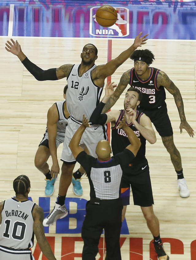 San Antonio Spurs' LaMarcus Aldridge (12) goes for the ball during the tipoff in the first half of their regular-season NBA basketball game against the Phoenix Suns in Mexico City, Saturday, Dec. 14, 2019. (AP Photo/Rebecca Blackwell)