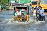 Residents travel in a van to cross a flooded street following heavy rains in Hyderabad on October 16, 2020. (Photo by NOAH SEELAM / AFP) (Photo by NOAH SEELAM/AFP via Getty Images)