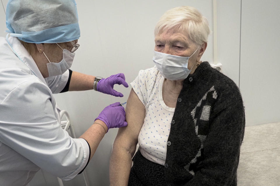 """A Russian medical worker administers a shot of Russia's Sputnik V coronavirus vaccine to Galina Shilova in a local rural medical post in the village of Ikhala in Russia's Karelia region, Tuesday, Feb. 16, 2021. """"When you watch TV and see how people are suffering … you don't want that. You want to live a little longer,"""" Shilova said. (AP Photo/Dmitri Lovetsky)"""