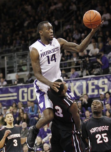 Washington's Tony Wroten (14) collides with Cal State Northridge's Jordan Mitchell in the second half of an NCAA college basketball game Thursday, Dec. 22, 2011, in Seattle. Wroten was called for a player control foul on the play. Washington won 74-51. (AP Photo/Elaine Thompson)