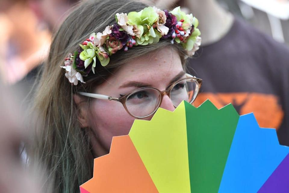 A woman with a flower crown peeps over a rainbow-coloured fan