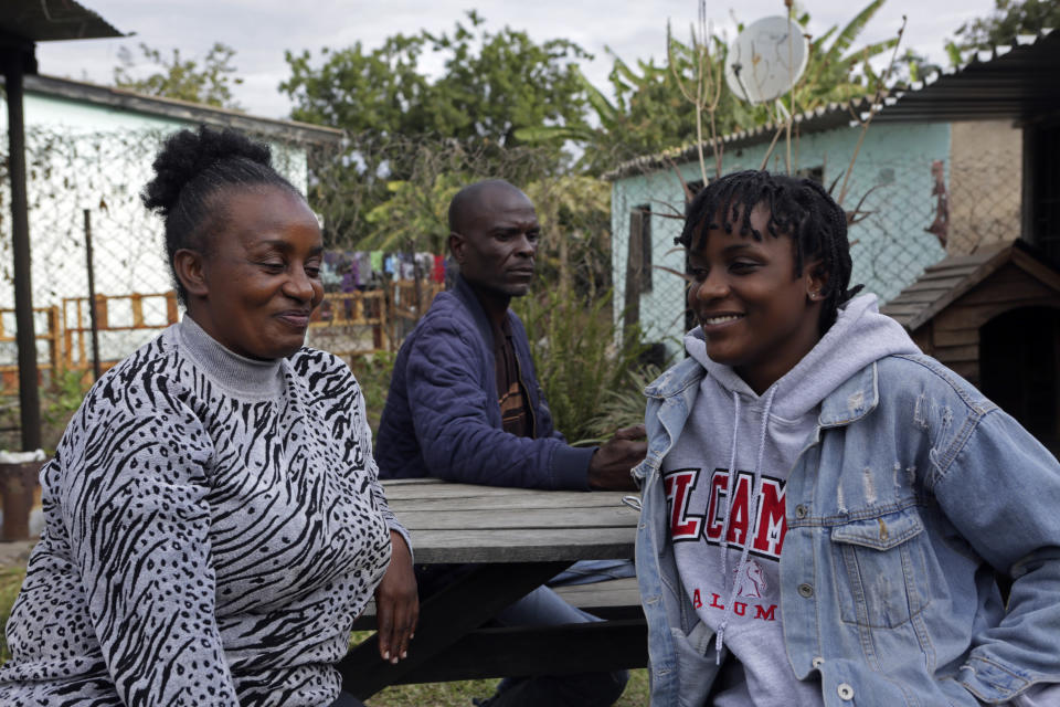 Andrew Ngwenya, center; his wife, De-egma, left, and their daughter sit outside their home in a working class township in Harare, the capital Zimbabwe, on Monday, July, 12, 2021. Ngwenya and his wife went to a hospital that sometimes had spare doses of COVID-19 vaccine, only to be turned away due to shortages. (AP Photo/Tsvangirayi Mukwazhi)