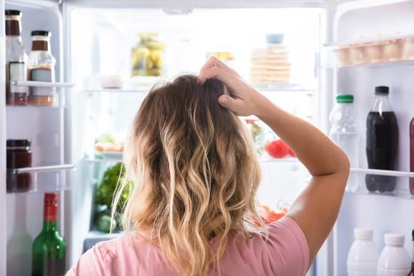Rear view of a woman scratching her head while looking in open refrigerator