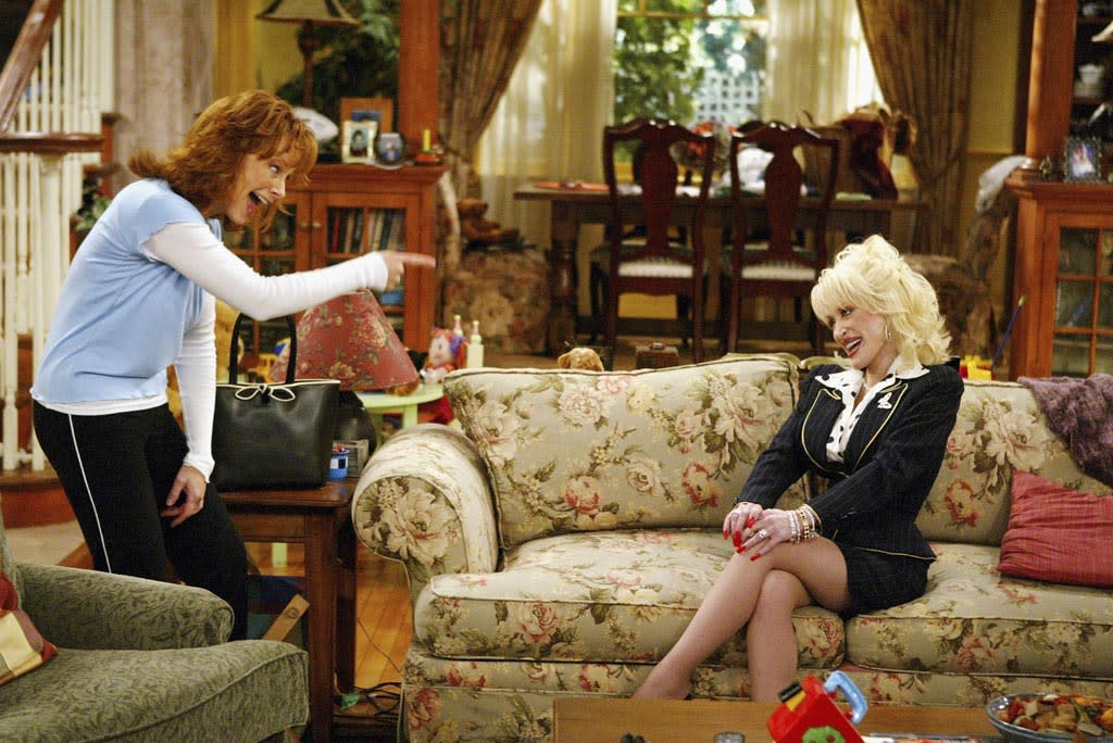 "LOS ANGELES - FEBRUARY 15:  Actress/singer Reba McEntire (L) and singer Dolly Parton appear on the set of The WB's ""Reba"" at 20th Century Fox Studios on February 15, 2005 in Los Angeles, California. (Photo by Kevin Winter/Getty Images) *** Local Caption *** Dolly Parton;Reba McEntire"