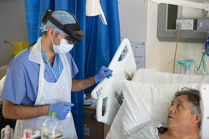 A doctor talks to a patient while wearing the HoloLens.