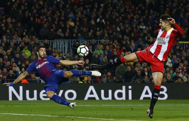 FC Barcelona's Luis Suarez, left, duels for the ball against Girona's Juanpe Ramirez during the Spanish La Liga soccer match between FC Barcelona and Girona at the Camp Nou stadium in Barcelona, Spain, Saturday, Feb. 24, 2018. (AP Photo/Manu Fernandez)