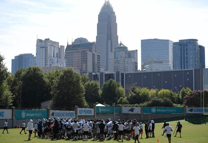 The Charlotte skyline rises in the background as the Carolina Panthers practice during training camp on Tuesday, August 18, 2020.