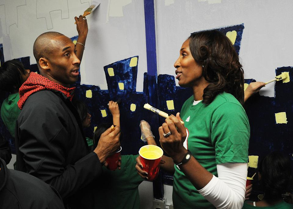 """NBA star Kobe Bryant from the Los Angeles Lakers, is helped by Lisa Leslie from the WNBA as they participate in the """"City Year School Refurbishment Project"""" at the Virgil Middle School in Los Angeles on February 18, 2011.  The project is part of the """"2011 NBA Cares All-Star Day of Service""""  where current and past NBA players help the community before the weekends All-Star game at the Staples Center.       AFP PHOTO/Mark RALSTON (Photo credit should read MARK RALSTON/AFP via Getty Images)"""