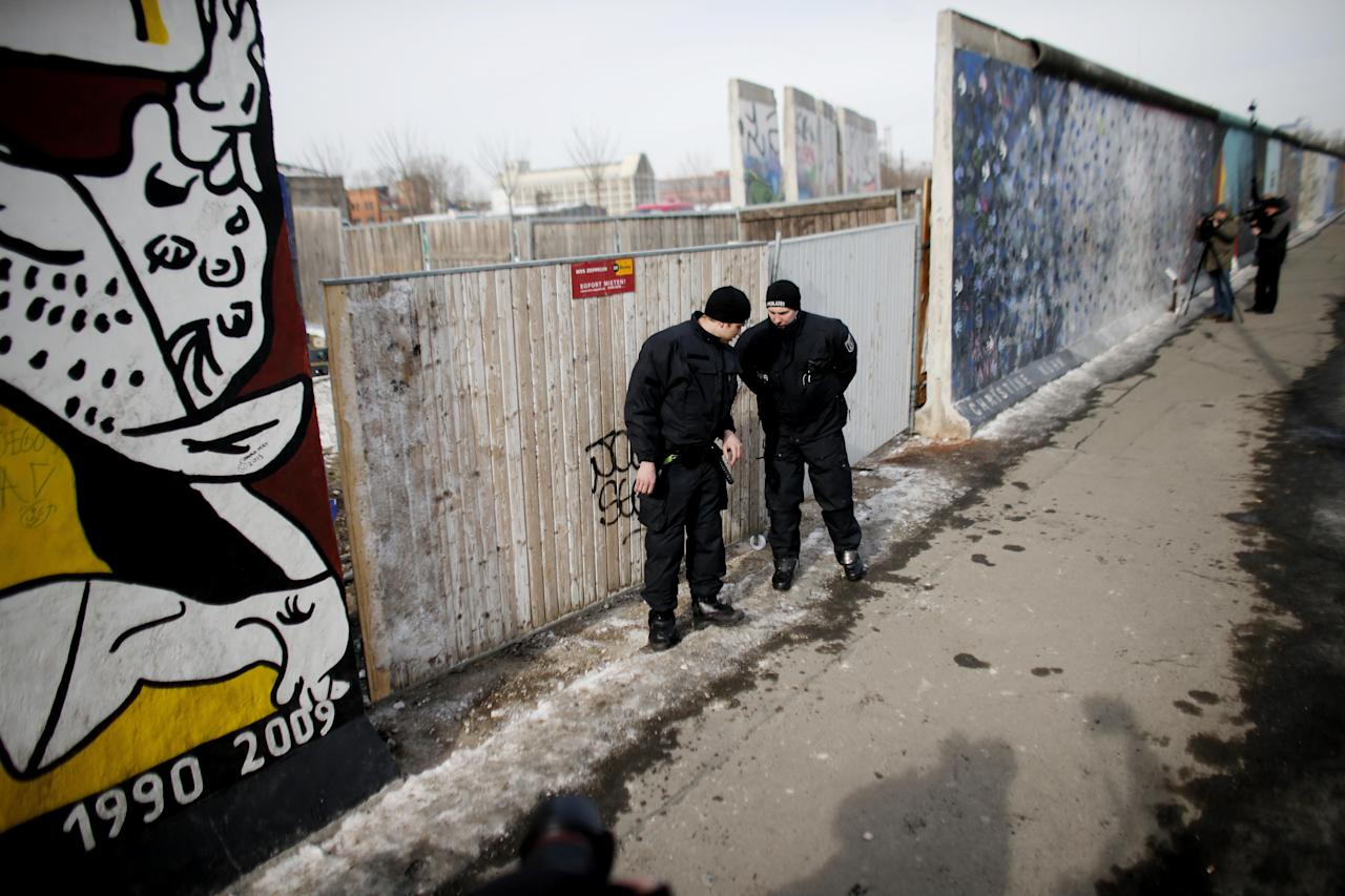 Police officers guard a construction site and sections of the East Side Gallery, while parts of the former Berlin Wall are removed in Berlin, Germany, Wednesday March 27, 2013. Work crews backed by about 250 police have removed portions of the Berlin Wall known as the East Side Gallery to make way for an upscale building project, despite demands by protesters that the site be preserved. Plans to remove part of the 1.3-kilometer (3/4-mile) stretch of wall sparked protests that developers were sacrificing history for profit. (AP Photo/Markus Schreiber