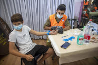 """An Israeli soldier conducts a COVID-19 antibody test on a boy in Hadera, Israel, Monday, Aug. 23, 2021. Ahead of the opening of the school year on Sept. 1, the Israeli army's Home Front Command is conducting serology tests on children age 3-12 who have not yet tested positive for coronavirus and are not yet listed as recovered, to see if they have antibodies. If a child tests positive for coronavirus antibodies, they can be issued a """"green pass,"""" allowing them to attend classes in-person. (AP Photo/Ariel Schalit)"""