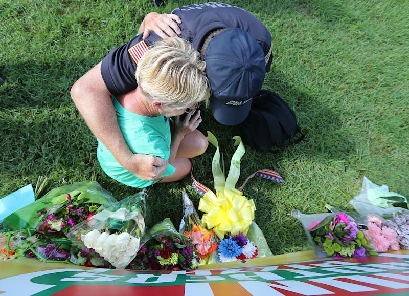 <p>Millville Police Chaplain Bob Ossler prays and weeps with a local resident as she places flowers on a memorial at the B-Quik gas station on Monday, July 18, 2016, in Baton Rouge, a day after a shooting at the scene that killed and wounded multiple police officers. (Curtis Compton/Atlanta Journal-Constitution via AP)</p>