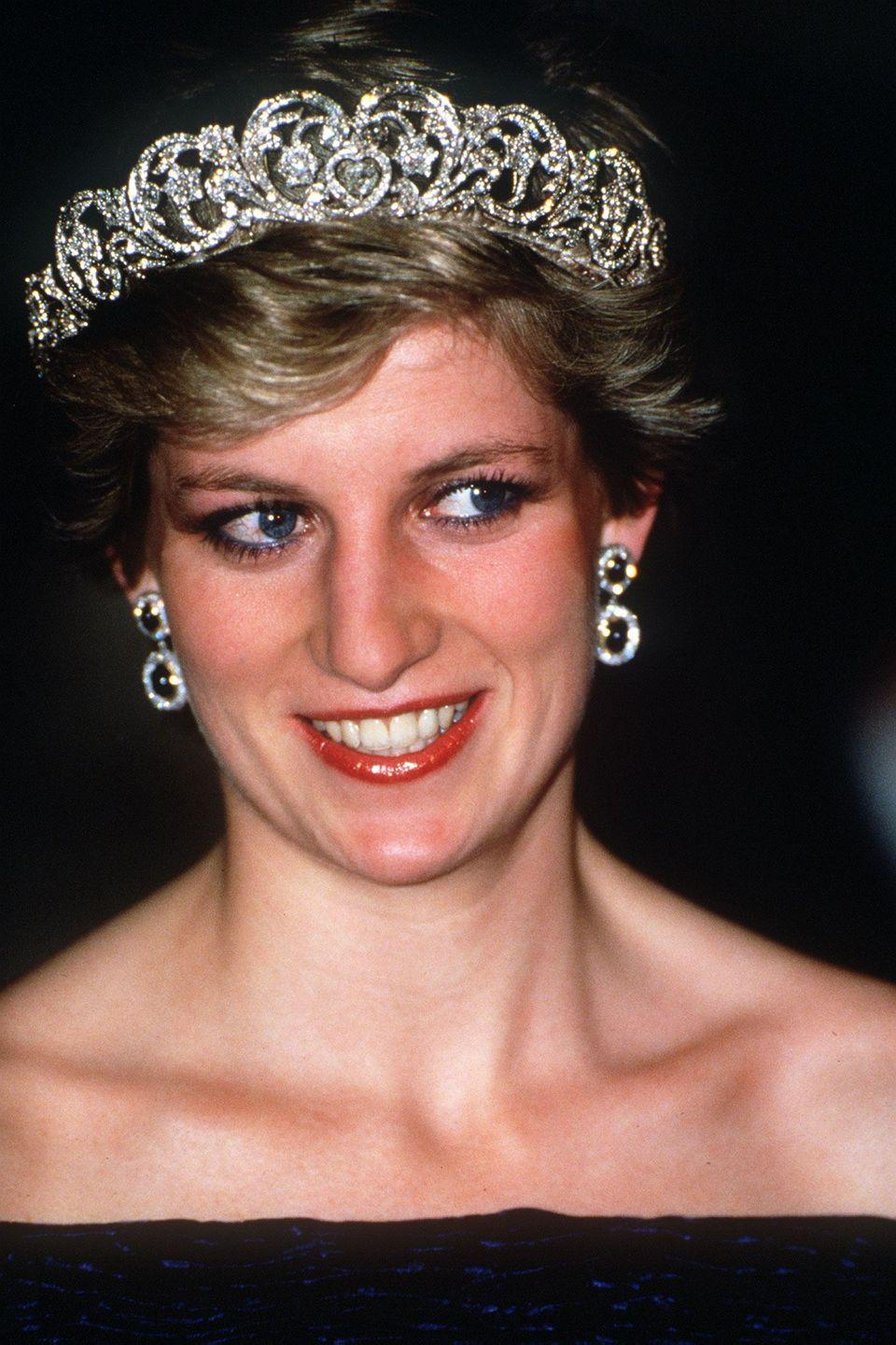 <p>On her official visit to Portugal, Diana stunned in an off-the-shoulder black gown, the Spencer tiara, circular drop earrings, and a bold red lip. </p>