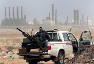 "FILE - In this March 5, 2011 file photo, an anti-government rebel sits with an anti-aircraft weapon in front an oil refinery in Ras Lanouf, eastern Libya. The United Nations said Friday, Oct. 23, 2020, that the two sides in Libyan military talks had reached a ""historic achievement"" with a permanent cease-fire agreement across the war-torn North African country. (AP Photo/Hussein Malla, File)"