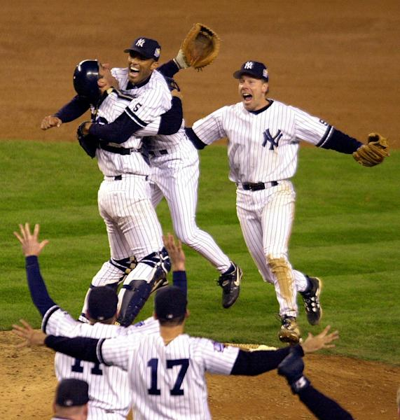 FILE - In this Oct. 27, 1999, file photo New York Yankees catcher Jorge Posada, left rear, and third baseman Scott Brosius, right rear, rush pitcher Mariano Rivera as teammates run to the mound after the Yankees beat the Atlanta Braves 4-1 in Game 4 of the World Series to sweep the series in New York. The teams with the best records in each league used to meet in the World Series every year. Now it's a rarity. Boston and St. Louis are the first since 1999, when the New York Yankees swept Atlanta. (AP Photo/Ron Frehm, File)