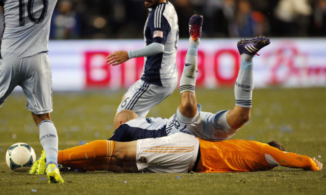 Sporting KC defender Aurelien Collin (78) is tripped by Houston defender Warren Creavalle, bottom, during the first half of an MLS playoff soccer match in Kansas City, Kan., Saturday, Nov. 23, 2013. (AP Photo/Orlin Wagner)