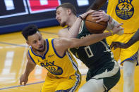 Milwaukee Bucks guard Donte DiVincenzo (0) is defended by Golden State Warriors guard Stephen Curry during the first half of an NBA basketball game in San Francisco, Tuesday, April 6, 2021. (AP Photo/Jeff Chiu)